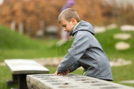 Photo pour Jeune garçon caucasien jouant mancala à l'extérieur au printemps. Les marques de commerce sur la veste ont été retirées . - image libre de droit