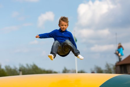 Boy jumping up and down on bouncy pad. Trademarks ...