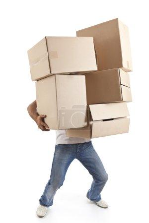 Photo pour Jeune homme transportant et laissant tomber sa pile de boîtes de déménagement - image libre de droit
