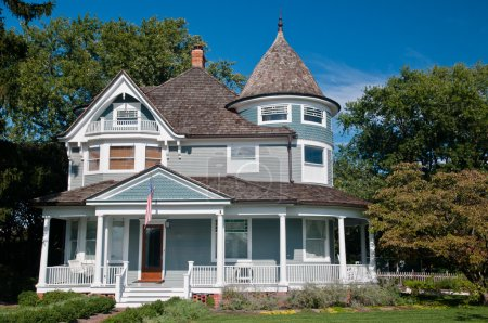Photo for Beautiful gray traditional victorian house. House has an American Flag haning over the porch and shows a beautiful garden with flowers and trees. Set against a cloudless blue sky - Royalty Free Image