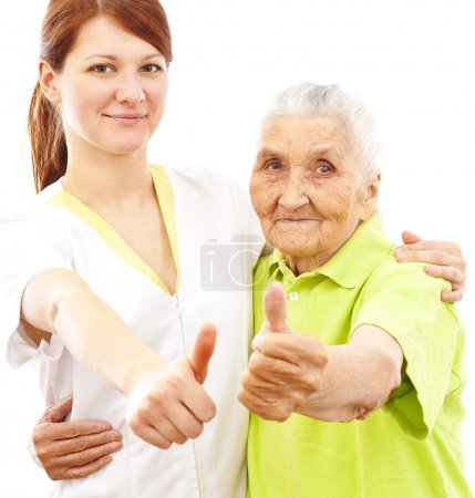 A young female doctor and a very old woman showing...