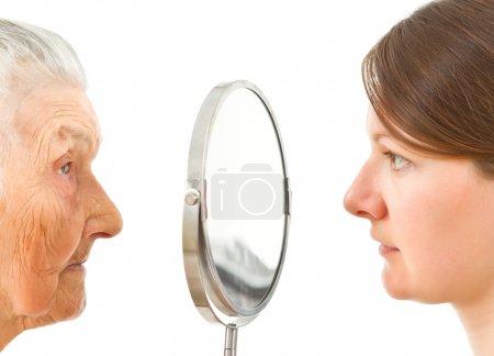 Foto de Jóvenes y viejos rostros aislados de pie en los dos lados del espejo - Imagen libre de derechos