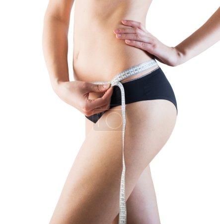 Sporty woman with slim body measuring waistline