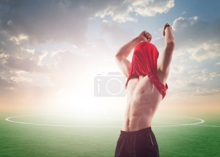 celebrating sportsman or soccer football player for world cup scoring goal and winning in competition contest play, T - shirt on his head face, hands to the top