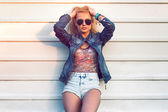 Outdoor summer closeup portrait of young stylish fashion glamorous woman or girl posed in  sunny day on street jeans jacket and sunglasses standing near white wall