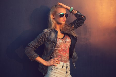 Outdoor summer closeup portrait of young stylish fashion glamorous woman or girl in  sunny day on street jeans jacket and sunglasses standing near blue wall