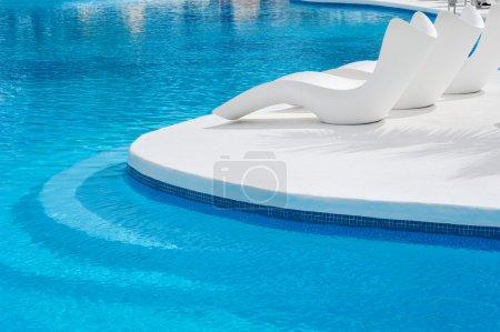 Photo pour Transats près d'une piscine pour se détendre - image libre de droit