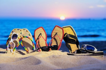 Photo for Three pair of beach sandals and glasses on the sandy beach - Royalty Free Image