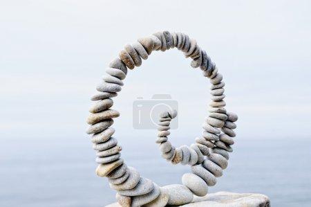 Photo pour Spirale blanche de cailloux sur le rocher à la mer - image libre de droit