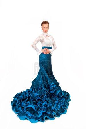 Young beautiful woman in blue dress dancing flamenco.