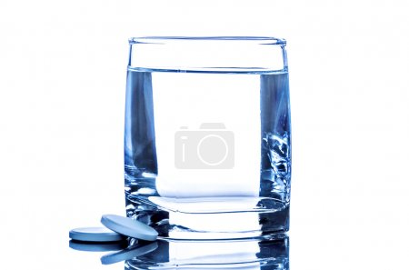 Two tablet near glass of water