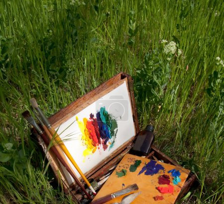 Painter's case on grass with palette, artistic tools and abstract painting