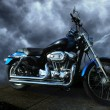 Riderless motorcycle. Clean, shiny, sparkling paint and chrome. Dynamic storm cloud background.
