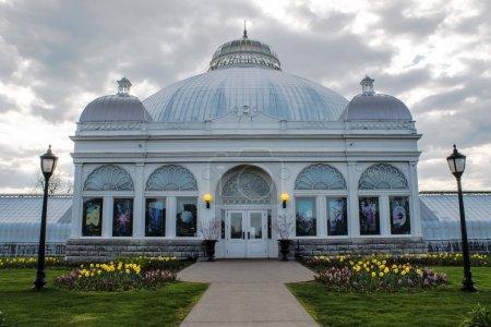 Photo pour Magnifique structure de serre avec toit à trois dômes et belles conceptions de fenêtres. Un assortiment de fleurs borde la promenade d'entrée du conservatoire. Des nuages argentés flottent au-dessus . - image libre de droit