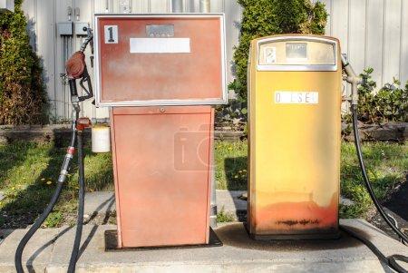 Photo pour Deux appareils de ravitaillement antiques. la peinture est émoussée et le lettrage est estomper. - image libre de droit