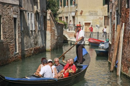 Venetian gondolier rowing gondola with passengers and speaking to somebody by cellphone