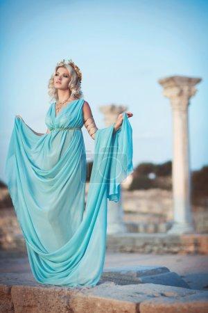 Frau im griechischen Stil bei Sonnenuntergang in der Nähe antiker Ruinen.