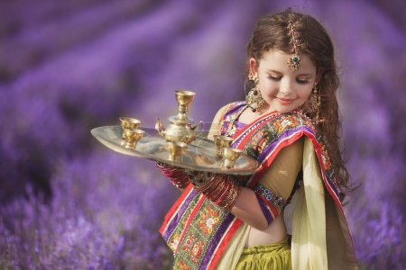 Indian girl with traditional plate of religious offerings