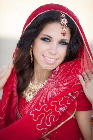 Beautiful Indian Woman in Traditional red dress and golden jewelry outdoors