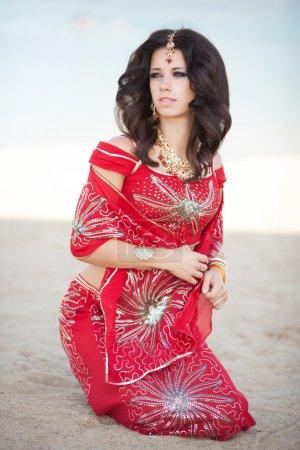 Photo pour Belle femme indienne en robe rouge traditionnelle et bijoux en or à l'extérieur. Portrait de jeune jolie fille indienne . - image libre de droit
