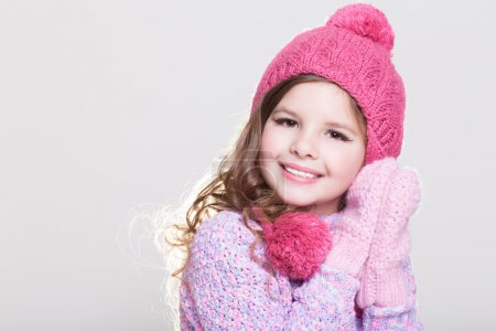 Photo for Cute little girl in winter woolen accessories. Adorable baby girl portrait in studio. Happy Little girl in winter hat and gloves. Space and white background. - Royalty Free Image