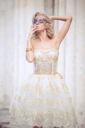 Photo pour Portrait de style vogue de belle femme délicate dans le masque de Venise et de la robe à la mode. femme sexy en plein air masque de carnaval et de robe de soirée. flou artistique. - image libre de droit