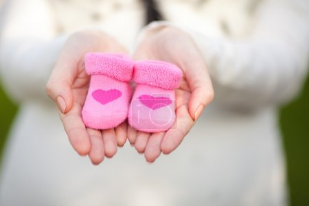 Pregnant woman belly holding pink baby booties