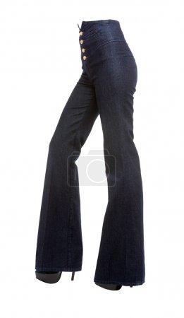 Photo pour Jambes de la jeune femme avec bell de quatre boutons d'or bas jeans et stilettos plate-forme isolés sur fond blanc. tracé de détourage inclus. - image libre de droit