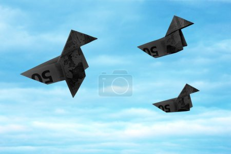 Photo for Black bank note origami birds flying away on blue sky. Abstract concept of black money flying away during crisis. - Royalty Free Image