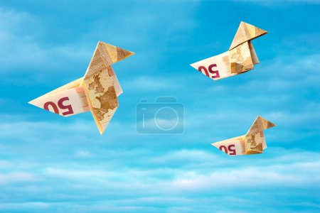 Bank note paper birds flying away on blue sky. Abs...