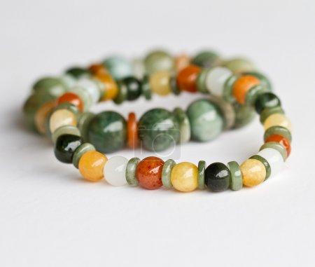 Foto de Coloridas pulseras de jade sobre fondo blanco - Imagen libre de derechos