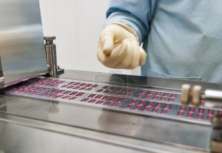 Photo pour Production pharmaceutique avec machine d'emballage bliser et main humaine dans des gants - image libre de droit