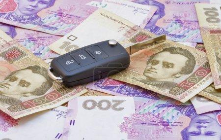 Car keys over Ukrainian banknotes