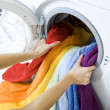 Woman taking color clothes from washing machine...
