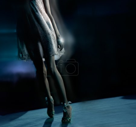 Photo for Beautiful model legs at the fashion show (blurred, in dark background) - Royalty Free Image