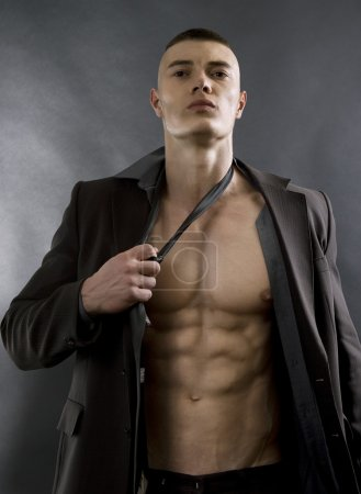 Young sexy man with athletic body posing on black background.