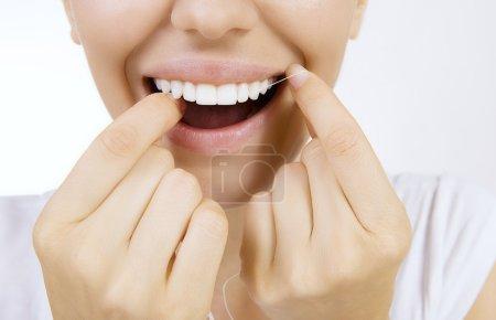 Photo pour Femme et les dents fil dentaire - Jeune femme caucasienne fil dentaire (gros plan femme sourire ) - image libre de droit