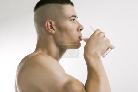 Athletic young man with protein shake, isolated on...