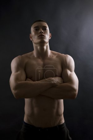 Young sexy man with athletic body on black background