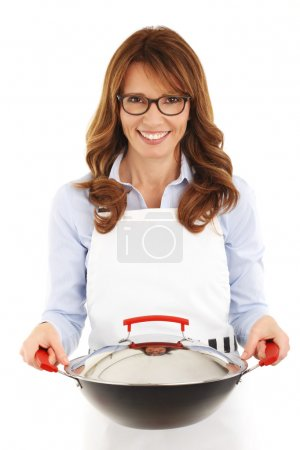 Pretty housewife holding a wok