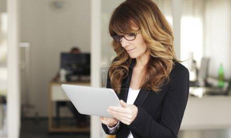 Photo pour Femme mature avec une tablette numérique au bureau - image libre de droit