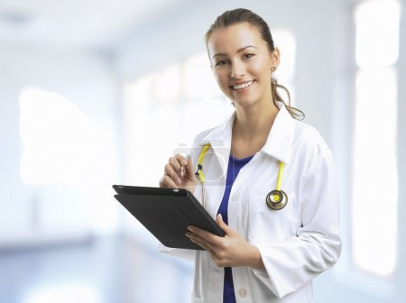 Photo for Female Doctor Standing At The Hospital With A Digital Tablet - Royalty Free Image