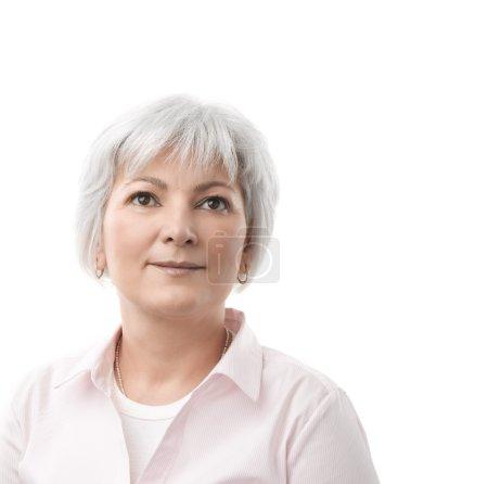 Foto de Una mujer senior feliz mirando hacia arriba y pensando o contemplar. aislado sobre un fondo blanco con espacio de copia. - Imagen libre de derechos