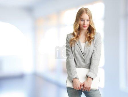 Photo pour Jeune femme d'affaires debout dans le bureau et tenant un ordinateur portable dans sa main - image libre de droit