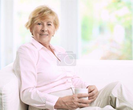 Photo pour Heureuse femme senior, assise sur un canapé pendant qu'elle boit une tasse de café - image libre de droit