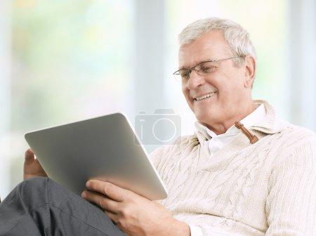 Photo pour Senior homme d'affaires travaillant à la maison avec sa tablette numérique - image libre de droit