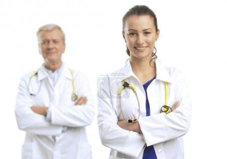 Photo pour Two doctors standing with arms crossed against white background. (stethoscope in neck) - image libre de droit