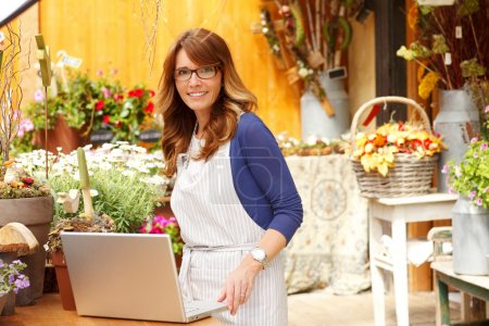 Photo for Smiling Mature Woman Florist Small Business Flower Shop Owner. She is using laptop to take orders for her store. Shallow Focus. - Royalty Free Image