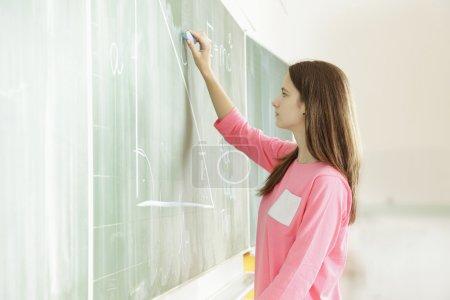 Portrait of schoolgirl at the blackboard