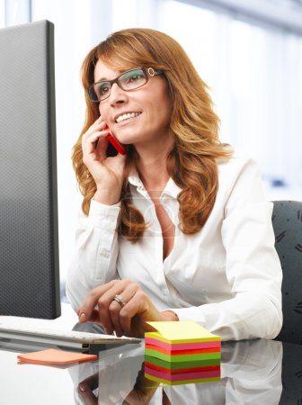 Smiling businesswoman on the phone in office